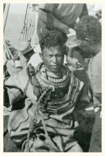 Malay diver in a diving suit, on board a ship, 1930